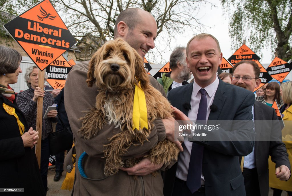 Liberal Democrats party leader Tim Farron walks over to pet cockapoo dog 'Bonnie' as he is campaigning for the British general election at Eastfield regeneration site on April 27, 2017 in Cambridge, England. Mr Farron has been campaigning in the Cambridgshire area alongside parliamentary candidate and former MP Julian Huppert, Mayoral candidate Rod Cantrill and cadidate for South Cambridgeshire Susan Van De Ven.