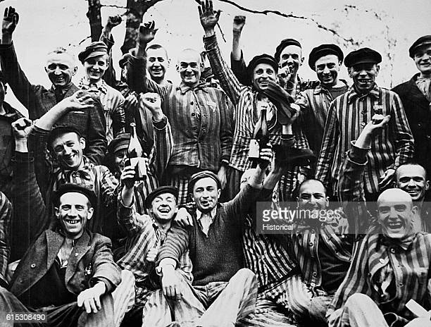 Liberated Polish inmates from the Dachau concentration camp raise bottles of wine and celebrate.