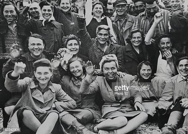 Liberated women prisoners of Dachau concentration camp wave and cheer after their liberation by troops of the 42nd and 45th Infantry Divisions of the...