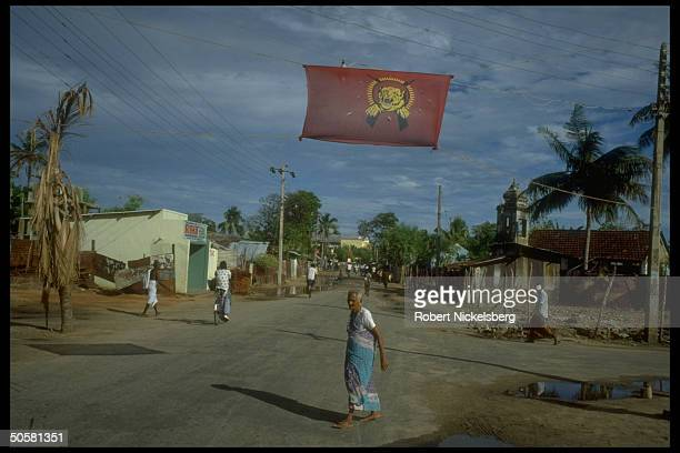 LTTE Liberation Tigers of Tamil Eelam red tiger flag stretched across street w locals in fore in Trincomalee Sri Lanka
