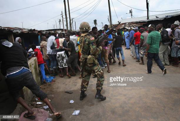 Liberian Army soldier part of the Ebola Task Force pushes back local residents while enforcing a quarantine on the West Point slum on August 20 2014...