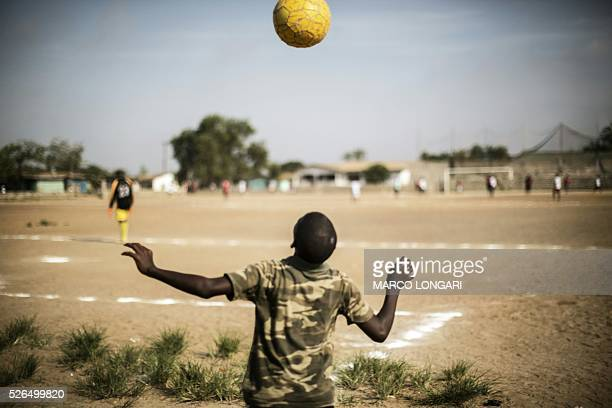 Liberian boy plays with a ball as international Liberian football star, George Weah plays a match on a dusty pitch at the Alpha Old Timers Sports...