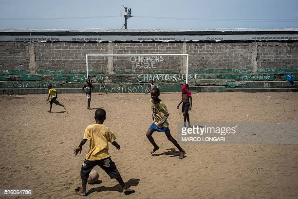 Liberian children play football on a sandy pitch outside the Star of the Sun Health Centre in the Monrovia township of West Point on April 29, 2016....