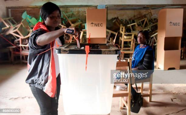 A Liberian election official looks on as a voter puts her ballot paper in a box at a polling station in Monrovia on December 26 for the second round...