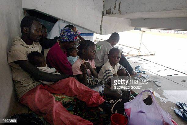 A Liberian family displaced by war as nearly 33000 people who took shelter at the Samuel Kanyon Doe stadium stands sit under stands in 14 July 2003...