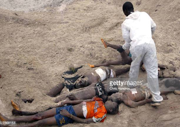 A Liberian from JFK Medical Center puts a boy's body in a mass grave of 66 bodies outside of Monrovia August 4 2003 in Liberia The hospital's morgue...
