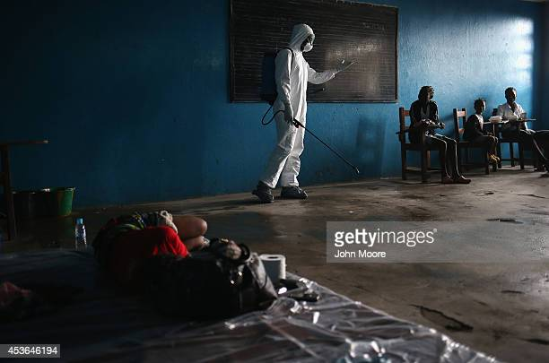 Liberian health worker speaks with families in a classroom now used as Ebola isolation ward on August 15 2014 in Monrovia Liberia People suspected of...