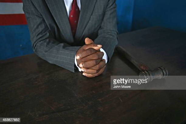 Liberian magistrate court judge Ernest Bana waits for a defense attorney to arrive to bring court into session on August 19 2014 in West Point...