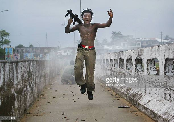 Liberian militia commander loyal to the government exults after firing a rocketpropelled grenade at rebel forces at a key strategic bridge July 20...