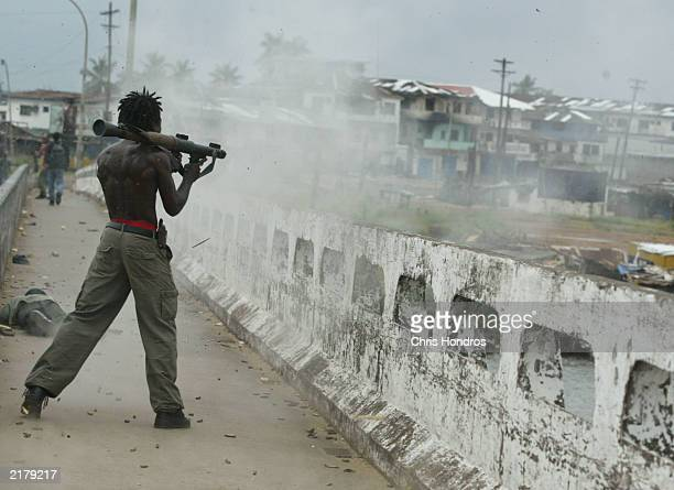 A Liberian militia soldier loyal to the government fires a rocket propelled grenade at rebel forces at a key strategic bridge July 20 2003 in...