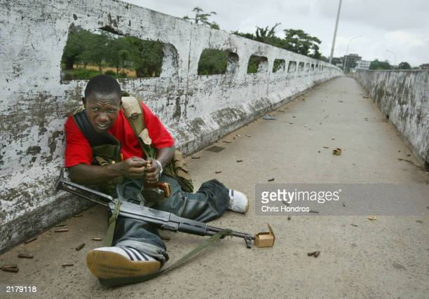 Liberian militia soldier loyal to the government reloads his magazines under enemy fire at a key strategic bridge July 20 2003 in Monrovia Liberia...