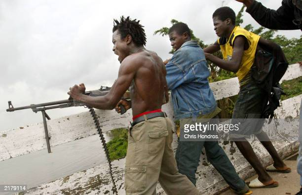 Liberian militia soldiers loyal to the government unleash machine gun fire at enemy rebel forces at a key strategic bridge July 20 2003 in Monrovia...