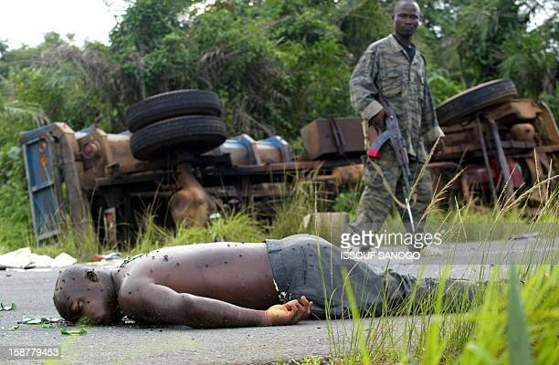 A Liberian militiaman of president Charles Taylor views the body of a rebel of the United for Reconciliation and Democracy 14 June 2003 after clashes...