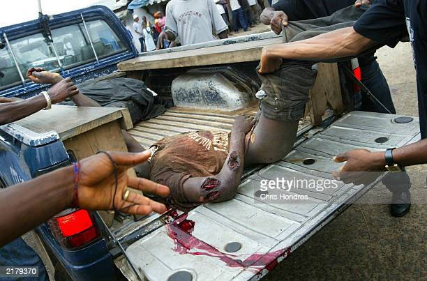 Liberian militiamen load the body of a rebel soldier outside a police station July 20 2003 in Monrovia Liberia Government forces succeeded in forcing...