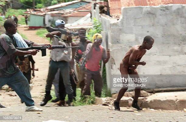 Liberian militiamen loyal to Charles Taylor's National Patriotic Front of Liberia execute 08 May 1996 an enemy Krahn fighter by shooting him in the...