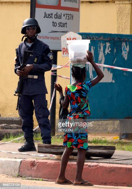 A Liberian policeman looks on as a young pedestrian walks in front of The National Elections Commission in Monrovia on December 28 2017 Initial...