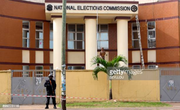 A Liberian policeman stands alert in front of The National Elections Commission in Monrovia on December 28 2017 Initial results are expected in...