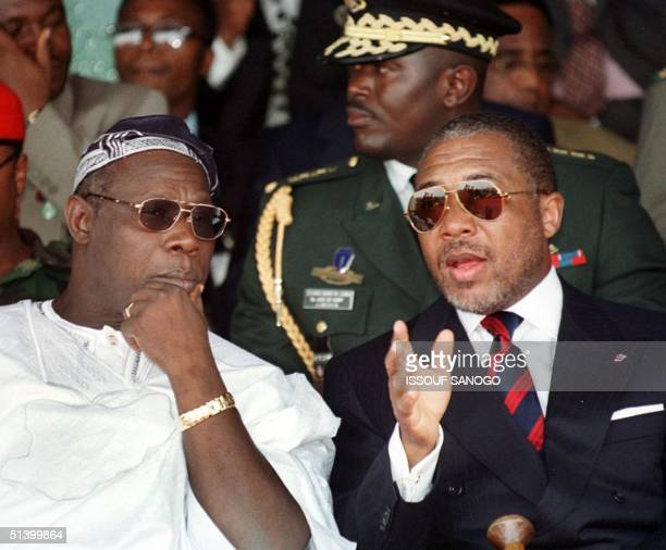 Liberian President Charles Taylor converses with his Nigeria's counterpart Olusegun Obasanjo during a symbolic bonfire to destroy some 1500 weapons...