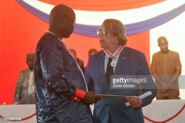 Liberian President George Weah gives Liberia's top honour to former French football player and coach Claude Le Roy during an official ceremony on...