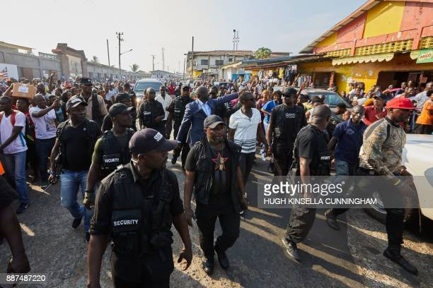 Liberian Presidential hopeful George Weah of the Coalition for Democratic Change waves to the crowd as he walks in Monrovia on December 6 2017 / AFP...