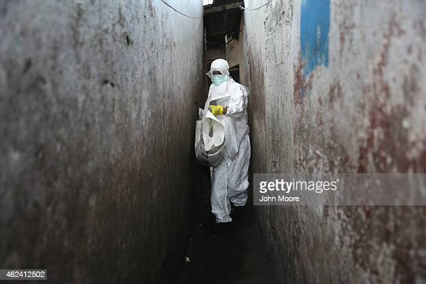 Liberian Red Cross burial team in Ebola protectant clothing collects the body of a toddler from a home in the West Point township on January 28 2015...
