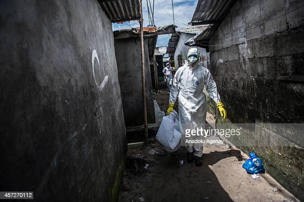 Liberian red cross health worker carries a plastic bag where body of 10monthold girl Asatu Kamba whose mum 27yearold Kumba Blama died suspectedly due...