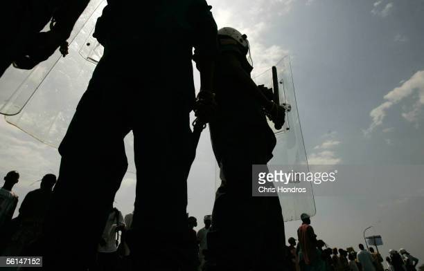 Liberian riot police stand guard in front of supporters of Liberian presidential candidate George Weah November 11 2005 in Monrovia Liberia Only a...