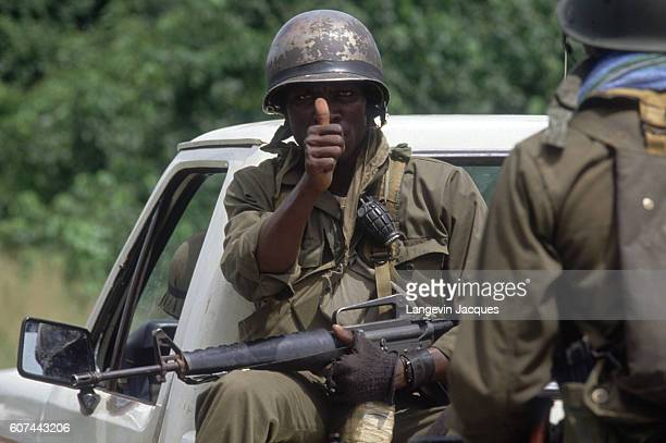 A Liberian soldier gives a thumbs up sign as he sits on the back of a pickup truck Liberian Army troops control the international airport and the...