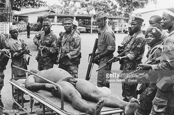 Liberian soldiers pose with their rifles around the displayed dead body of President Samuel Doe during the Liberian Civil War Prince Yormie Johnson...