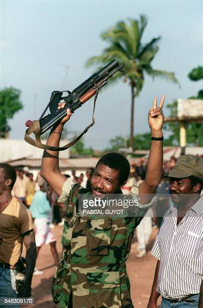 Liberian warlord Charles Taylor leader of the National Patriotic Front of Liberia holding machinegun waves and flashes V sign 10 July 1990 in...
