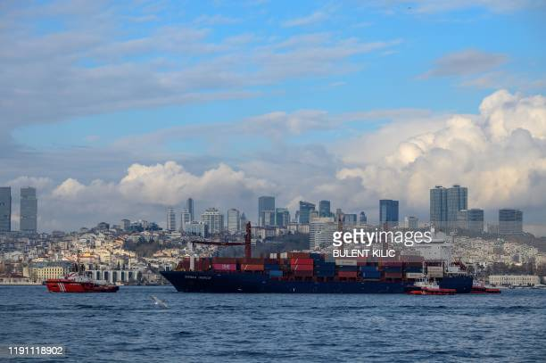 Liberian-flagged cargo vessel 'Songa Iridium' is tugged by a Coastal Safety boat after it ran ashore in the Bosphorus, on December 27 in Istanbul. -...