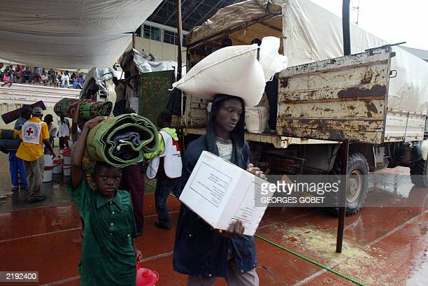 Liberians displaced by war carry goods in Samuel Kanyon Doe stadium in Monrovia 14 July 2003 following a goods and food distribution by the...
