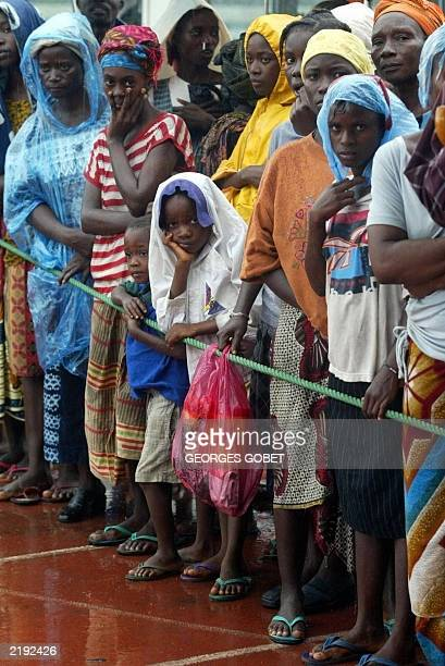 Liberians displaced by war who have sought shelter in Samuel Kanyon Doe stadium in Monrovia wait 14 July 2003 for the International Red Cross to...