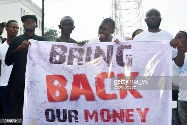 Liberians hold a banner during a demonstration over the disappearance of newly printed bills on September 24 in the capital Monrovia The cash nearly...