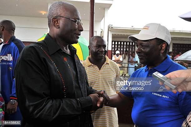 Liberia's candidate of the Congress for Democratic Change opposition party, Winston Tubman shakes hands with Carter Center Observer Chief, former...