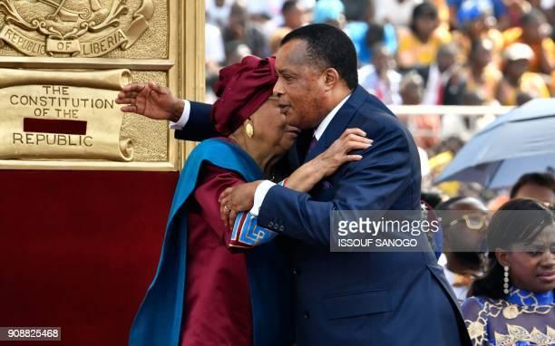 Liberia's outgoing president Ellen Johnson Sirleaf embraces Congo's President Denis Sassou Nguesso during the swearingin ceremony of Liberia's...