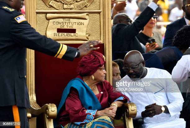 Liberia's outgoing president Ellen Johnson Sirleaf listens to Liberia's Presidentelect George Weah during Weah's swearingin ceremony on January 22...