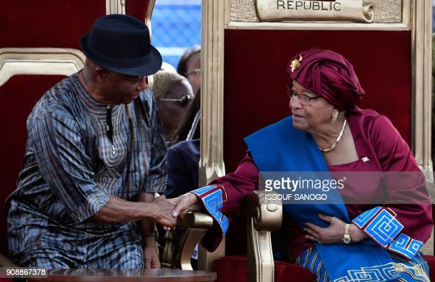 Liberia's outgoing President Ellen Johnson Sirleaf shakes hands with outgoing Vice President Joseph Boakai during the swearingin ceremony of...