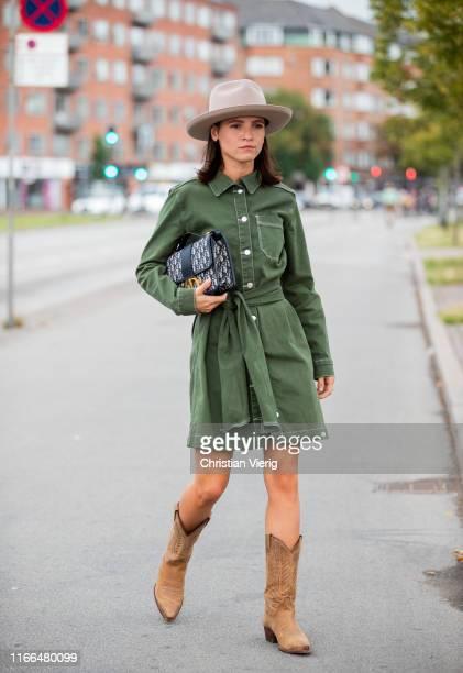 Liberta Haxhikadriu wearing green belted jeans dress hat Dior bag cowboy boots outside Blanche during Copenhagen Fashion Week Spring/Summer 2020 on...