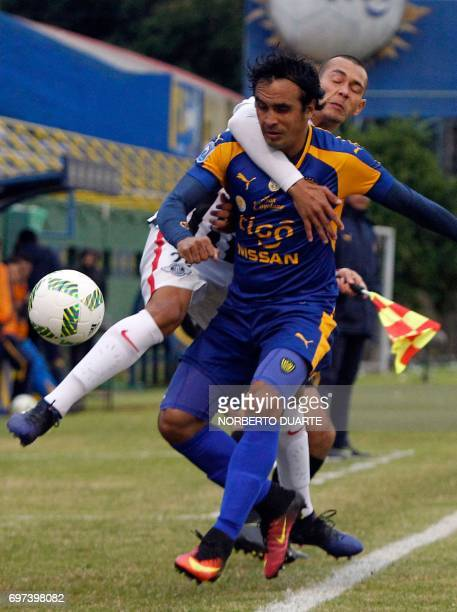 Libertad's footballer Antonio Bareiro vies for the ball with Blas Armoa of Sportivo Luqueno during their Paraguayan Apertura tournament match at the...