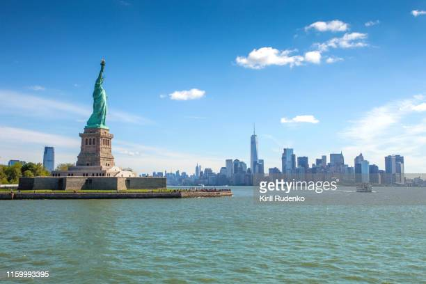 liberty island and the statue of liberty with the lower manhattan in background - statue of liberty stock pictures, royalty-free photos & images
