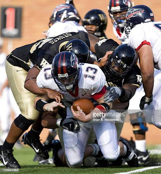 Liberty quarterback Brock Smith is sacked by Wake Forest linebacker Jyles Tucker and teammate Zach Stukes during second quarter action at Groves...