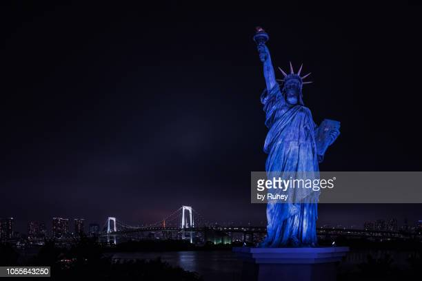 Liberty statue replica with the Tokyo skyline at the background by night