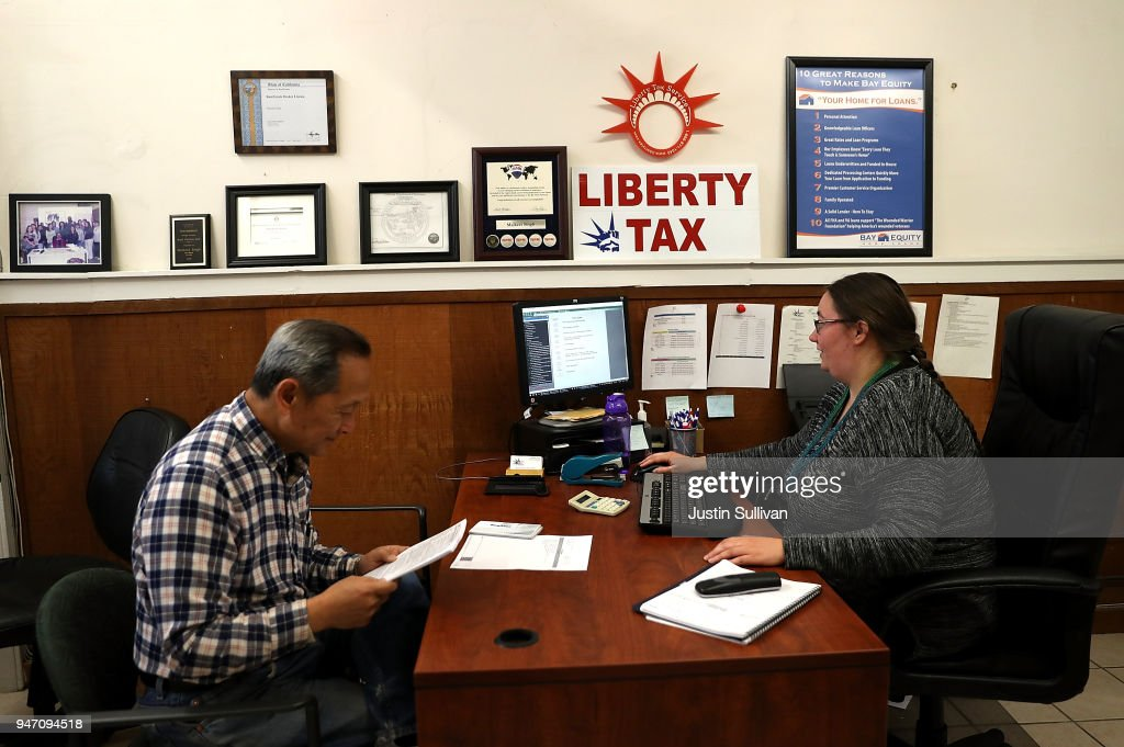 Liberty Tax Service tax specialist Laura Tuuri (R) helps a client do his taxes on April 16, 2018 in Oakland, California. Taxpayers who have procrastinated on filing their returns will have an additional two days to file tax returns since April 15th fell on a Sunday and Emancipation Day is observed on Moday April 16th.