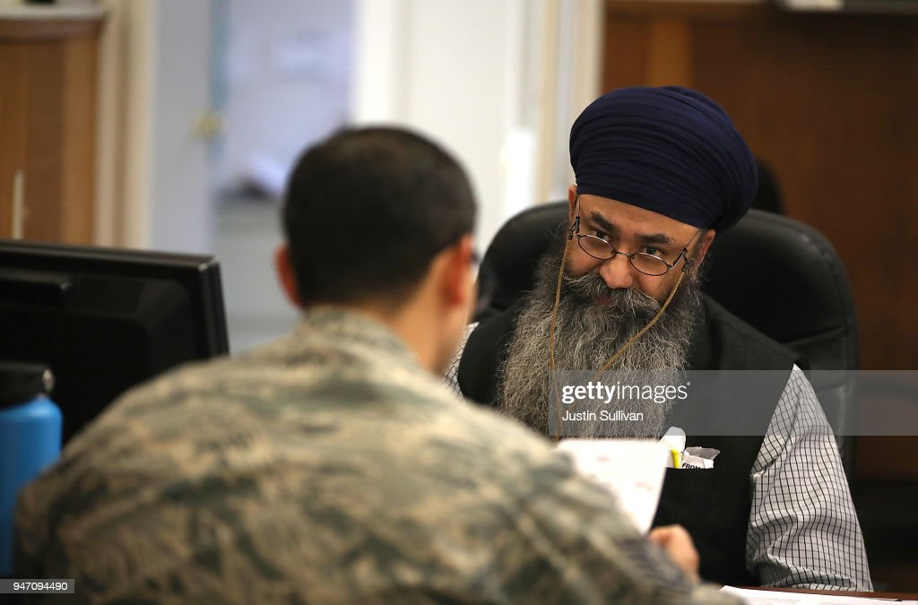 Liberty Tax Service tax specialist Malkeet Singh (R) helps a client do his taxes on April 16, 2018 in Oakland, California. Taxpayers who have procrastinated on filing their returns will have an additional two days to file tax returns since April 15th fell on a Sunday and Emancipation Day is observed on Moday April 16th.