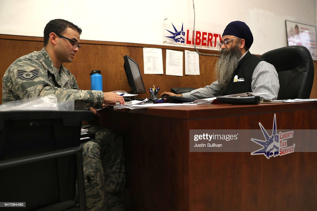 Liberty Tax Service tax specialist Malkeet Singh (R) helps Ikaika San Nicolas (L) do his taxes on April 16, 2018 in Oakland, California. Taxpayers who have procrastinated on filing their returns will have an additional two days to file tax returns since April 15th fell on a Sunday and Emancipation Day is observed on Moday April 16th.