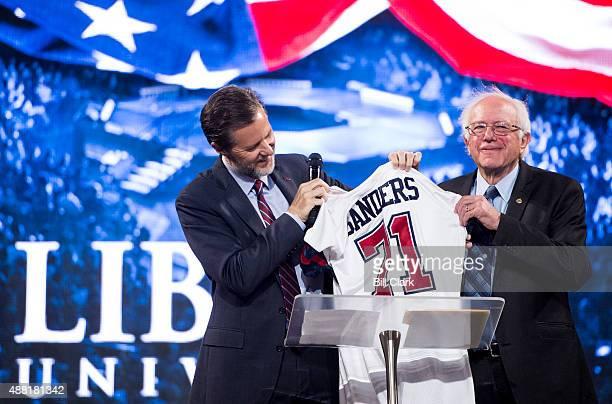 Liberty University president Jerry Falwell Jr presents a sports jersey to Presidential candidate Sen Bernie Sanders IVt before Sanders' speech at...