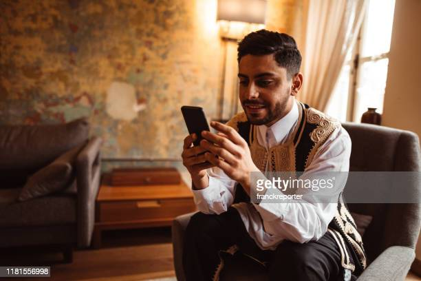 libic man using the smartphone at home - religious occupation stock pictures, royalty-free photos & images