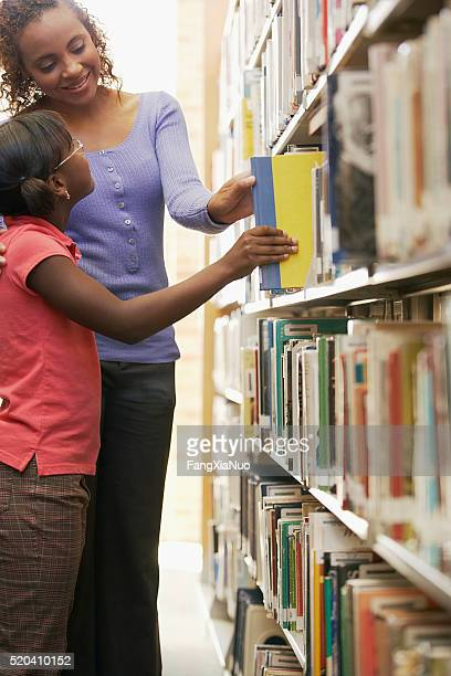 Librarian and young girl choosing a book