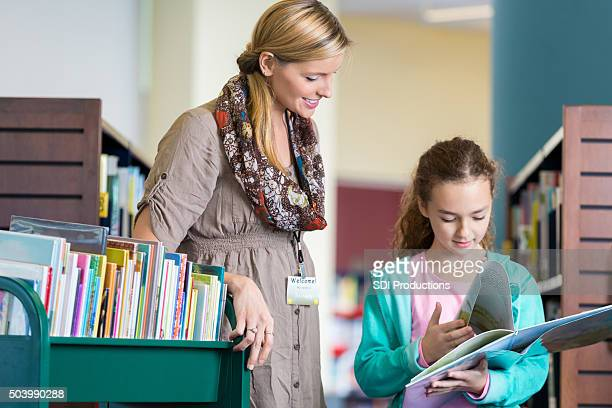 Librarian assisting elementary age little girl in library